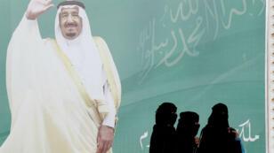 Des Saoudiennes passent devant le portrait du roi Salman bin Abdulaziz Al Saoud à Riyad, le 12 février 2018.