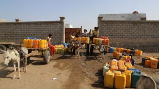 Des enfants remplissent des jerricanes d'eau dans la banlieue du port de Hodeidah, le 18 octobre 2016.