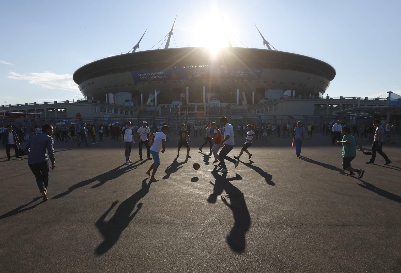 Solo queda un día para que los aficionados sigan disfrutando de la fiesta de la copa del mundo Rusia 2018. Un grupo de aficionados juegan fútbol en frente del Estadio de San Petersburgo.