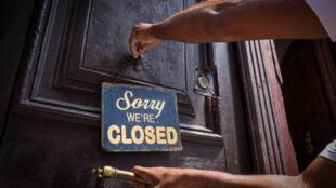 Un empleado cuelga un cartel frente a la puerta de un  café en La Habana, el 16 de marzo de 2020, en medio de la pandemia del nuevo coronavirus. El sector privado en Cuba está sufriendo la falta de turistas como consecuencia de la suspensión de actividades, para evitar la propagación de la enfermedad.