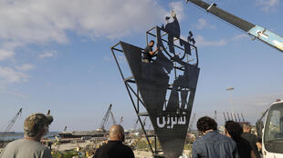 "Lebanese activists erect a monument on October 16, 2020, with the inscription ""October 17"" in Arabic, the first anniversary of the beginning of a nationwide anti-government protest movement, in front of the devastated port of the capital Beirut where a massive explosion took place more than two months ago."