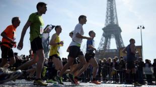 Des participants au Marathon en 2015 passent devant la Tour Eiffel.
