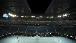 Le Serbe Novak Djokovic (d) affronte l'Américain Taylor Fritz, devant des tribunes désertées après 23h30, en raison du nouveau confinement démarrant à minuit, le 12 février 2021 lors de l'Open d'Australie à Melbourne