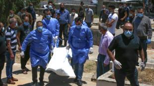 Le corps d'ue victime du Covid-19 est transporté par du personnel soignant à Hebron, le 5 juillet 202.