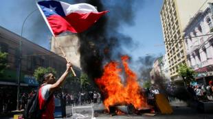 Un manifestant brandit un drapeau chilien dans les rues de Valparaiso, au Chili, le 24 octobre 2019.
