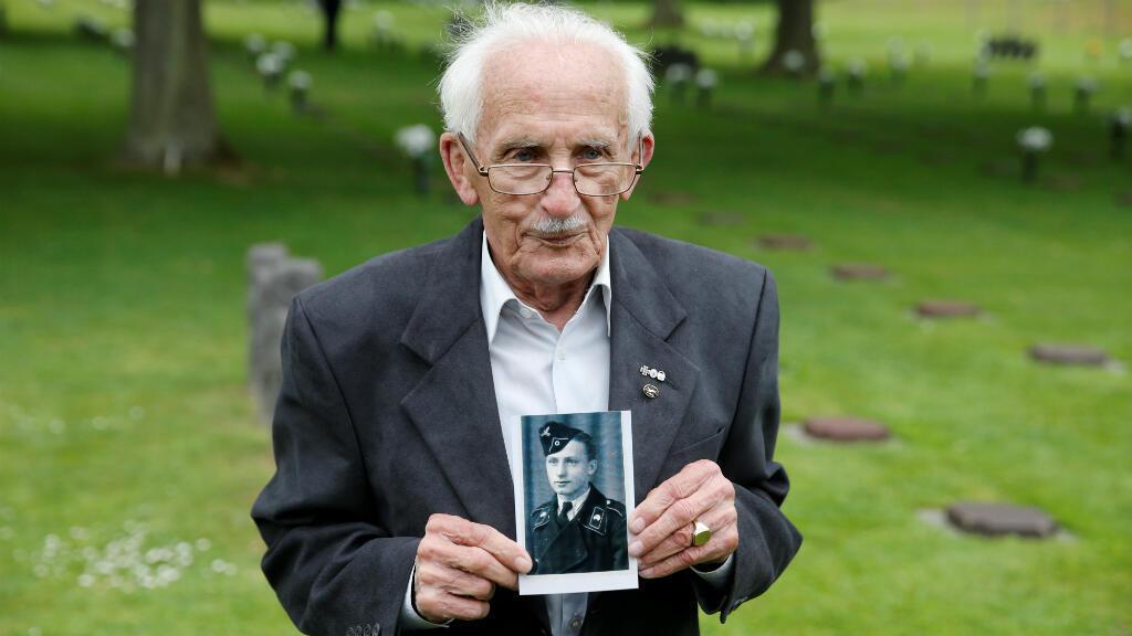Konrad Scheucher, un alemán veterano de la Segunda Guerra Mundial posa con una foto suya de joven en el cementerio de guerra alemán en La Cambe, en Normandía, Francia el 5 de junio de 2019, en medio de homenajes.