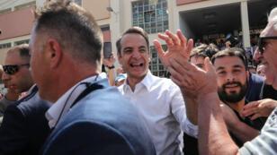 Kyriakos Mitsotakis, du parti conservateur Nouvelle-Démocratie (ND), est félicité par des partisans à la sortie des urnes à Athènes, le 7 juillet.