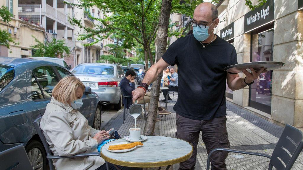 Una mujer desayuna en la terraza de una cafetería en Zaragoza, España, el 11 de mayo de 2020.