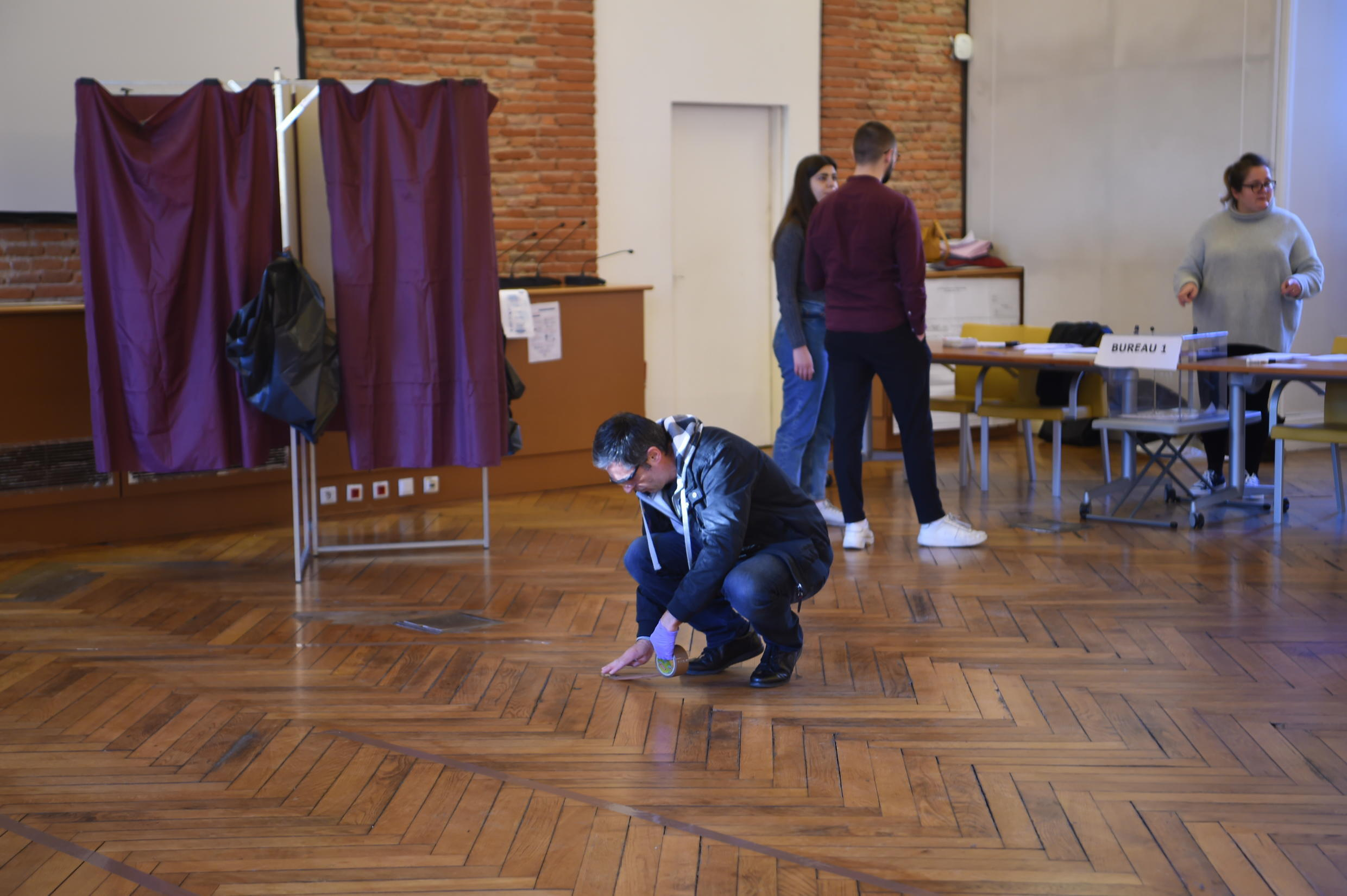 An electoral official marks the floor to encourage people to keep their distance while voting in municipal elections in Toulouse.