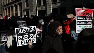 Personas portan carteles durante una marcha en la que piden Justicia por la muerte de George Floyd en la ciudad de Minneapolis, Estados Unidos, el 8 de marzo de 2021.