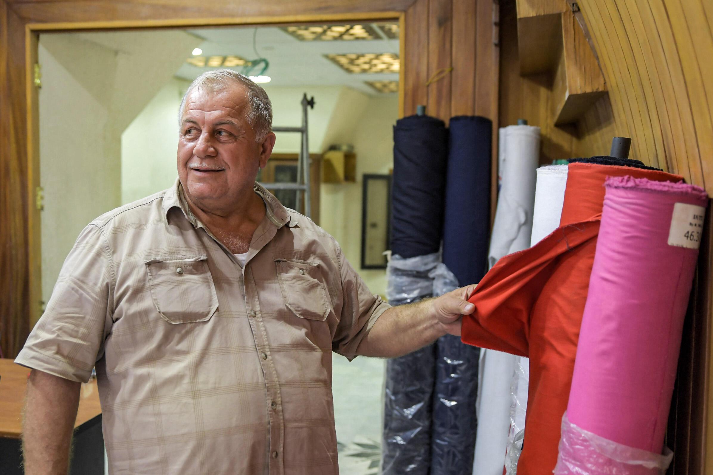 65 yaşındaki tekstil tüccarı Ahmed El-Damlakhi, pazardaki dükkânının içinde duruyor
