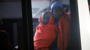 Una mujer y un niño migrante, interceptados frente a la costa en el mar Mediterráneo, observan mientras se sientan en un autobús después de llegar en un bote de rescate en el puerto de Málaga, sur de España, el 3 de enero de 2019.