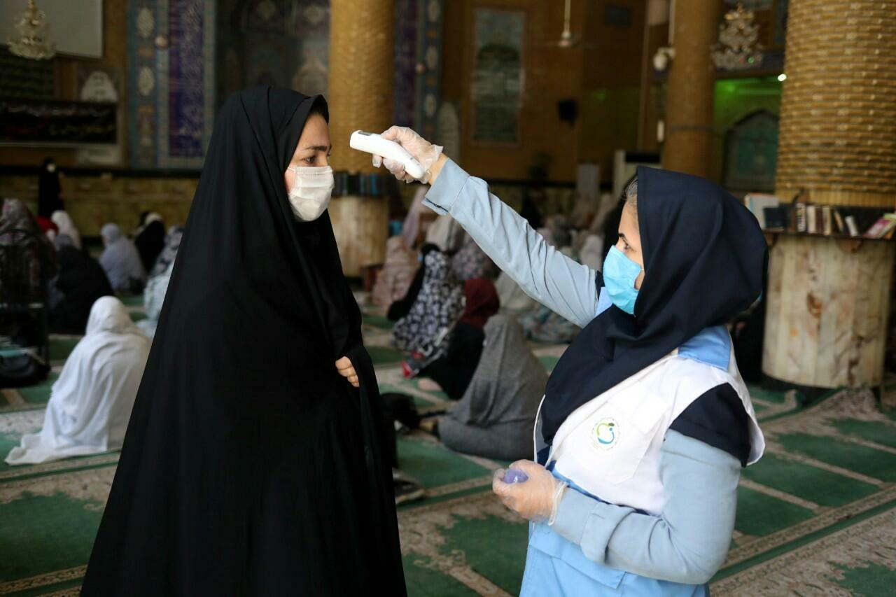 Una mujer mide la temperatura de otra en la entrada de una mezquita en Qarchak, Irán. 12 de junio de 2020.
