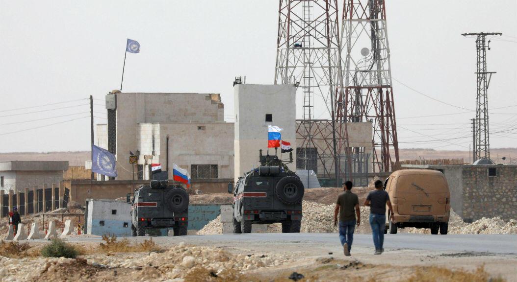 Banderas de Siria y Rusia, país que respalda a las fuerzas armadas de Bashar Al Assad, ondean sobre vehículos militares, en Manbij, norte de Siria, el 15 de octubre de 2019.