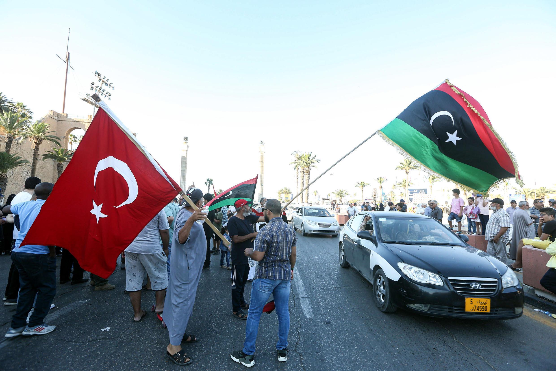 Des drapeaux de la Libye et de la Turquie agités lors d'une manifestation sur la Place des Martyrs au centre de la capitale libyenne, Tripoli, le 21 juin 2020.
