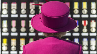 Elizabeth II observe des médailles anglaises datant du règne de la reine Victoria, en novembre 2015.