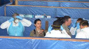 Des militaires américains enseignent au personnel médical libérien comment se protéger efficacement avant de soigner les malades d'Ebola.