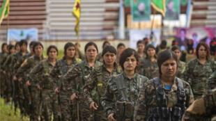 Combatientes de las unidades YPJ participan en un desfile militar el 27 de marzo de 2019, celebrando la eliminación total del último bastión del grupo Estado Islámico en el este de Siria.