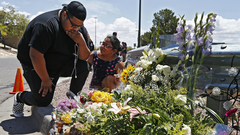 Brandon Lee Flores y Journie Lea Flores hacen una pausa por un momento después de colocar flores junto a un memorial por turnos a lo largo de la calle detrás de la escena de un tiroteo masivo en un Walmart en El Paso, Texas, el 4 de agosto de 2019.