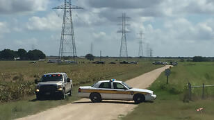 This handout photograph obtained courtesy of KXAN TV shows a police vehicle blocking a road where a hot air balloon crashed near Lockhart, Texas, July 30, 2016.