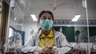 Una estudiante de último año, con mascarilla y tras una mampara de plástico individual, asiste a clase en una escuela de secundaria, el 6 de mayo de 2020 en la ciudad china de Wuhan