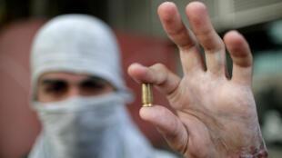Un partidario de la oposición sostiene una vainilla de una bala durante los enfrentamientos con las fuerzas de seguridad el 1 de mayo de 2019.