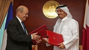"""Qatar's Foreign Minister Mohammed bin Abdulrahman Al-Thani (R) met with his French counterpart Jean-Yves Le Drian in Doha to sign the """"strategic dialogue"""" agreement on February 11, 2019"""
