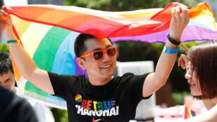 Un homme agitant le drapeau arc-en-ciel, emblême de la communauté LGBT, lors de la gay pride à Shanghai, le 17 juin 2017.