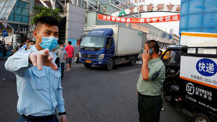 Security guards wearing face masks stand outside the Jingshen seafood market which has been closed for business after new coronavirus infections were detected, in Beijing, China June 12, 2020.