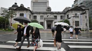 Des passants dans la rue à Séoul devant la banque centrale,le 23 juillet 2020