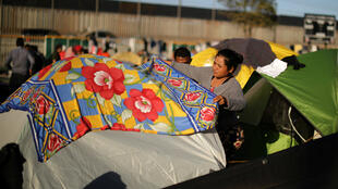 Una mujer, que hace parte de la caravana migrante, cubre su tienda de campaña en el refugio provisional en Tijuana el lunes 26 de noviembre de 2018.