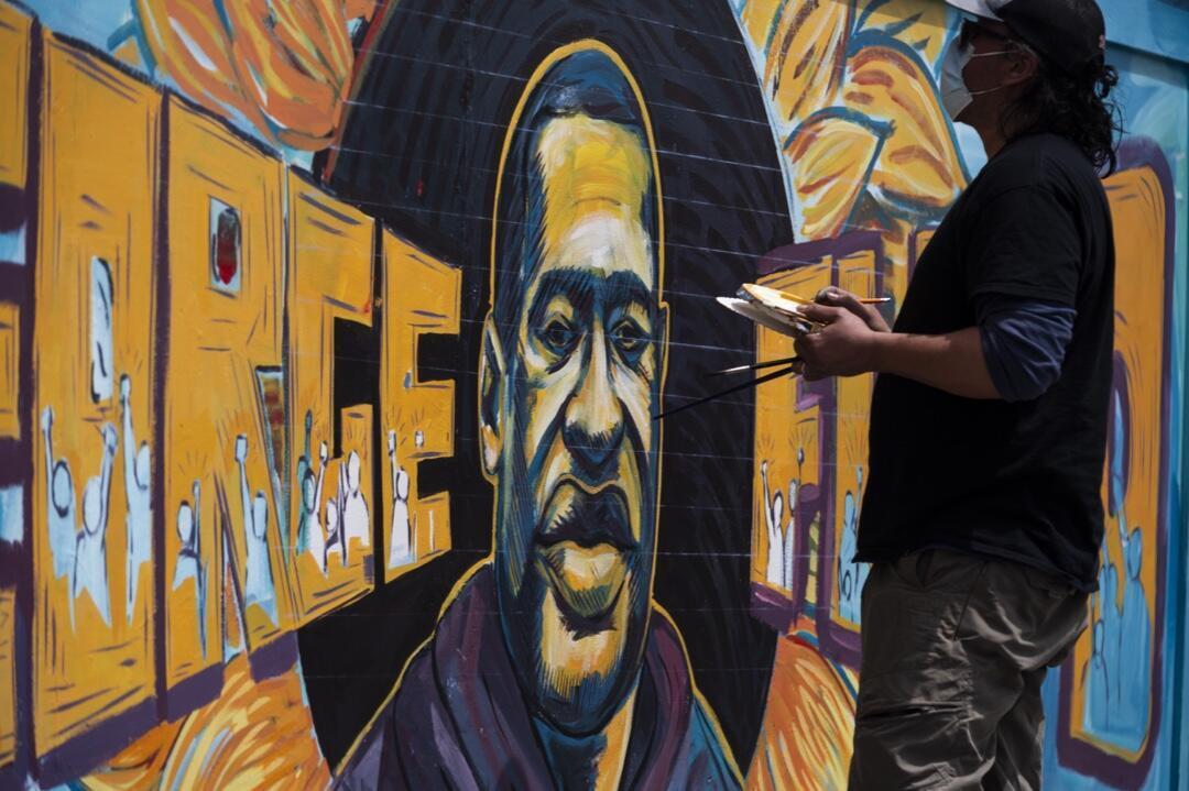 Un grupo de artistas pinta un mural de George Floyd el 28 de mayo de 2020 en la pared afuera de Cup Foods, donde murió bajo custodia policial en Minneapolis, Minnesota.