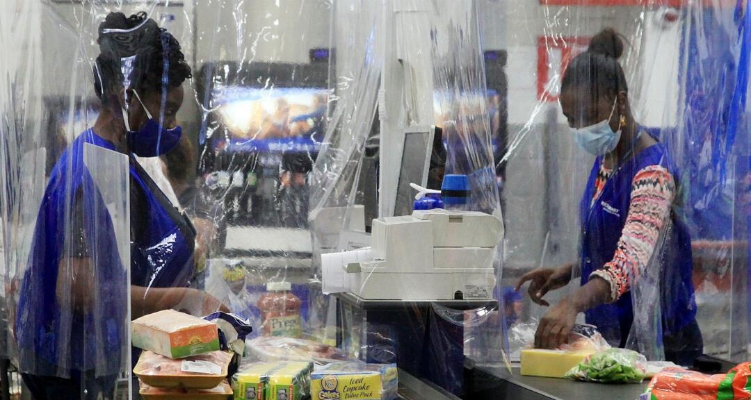 Una cajera atiende a una cliente, ambas cubiertas en un protector de plástico en un supermercado de Puerto España, Trinidad y Tobago, el 30 de abril de 2020.