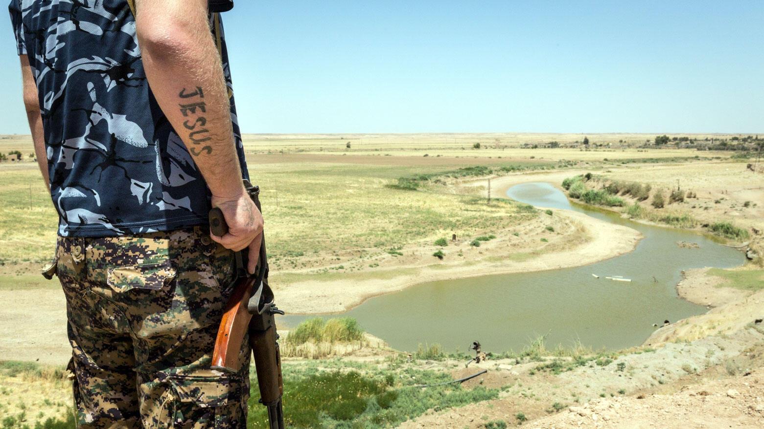 Un soldat de la milice MFS (Syriac Military Council), posté en haut d'une colline de Tall Tamr, non loin de la rivière du Khabour.