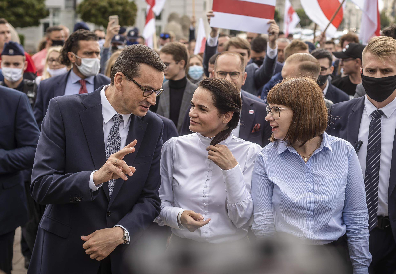 """La líder de la oposición, Svetlana Tikhanovskaya, camina con el primer ministro polaco Mateusz Morawiecki, después de decirle a los estudiantes universitarios de Varsovia que las manifestaciones en Belarús fueron """"históricas""""."""