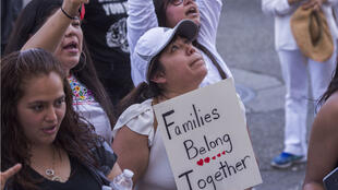 """Une femme brandit une pancarte """"les familles doivent restées unies"""" lors d'une manifestation en juin 2018 à Los Angeles contre la politique de séparation de l'administration Trump."""