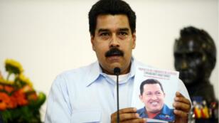 Nicolas Maduro tenant un portrait d'Hugo Chavez.