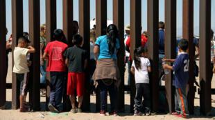 Los miembros de una caravana de migrantes de América Central y sus simpatizantes miran a través del muro fronterizo entre EE. UU. y México antes de presentar una solicitud de asilo, en San Diego, EE. UU. el 29 de abril de 2018.