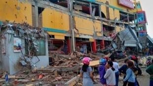 Habitantes de Palu, Indonesia, observan los daños de un centro comercial devastado por el tsunami registrado el viernes 29 de septiembre.