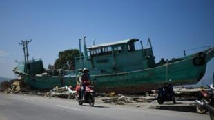 Dos persona conducen su moto en una calle de Palu, Indonesia, junto a un barco llevado a tierra por la acción del terremoto y el tsunami que golpearon el lugar el pasado 28 de septiembre
