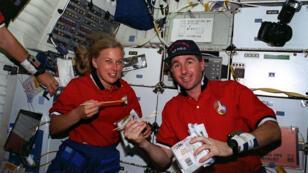 En août 1997, les astronautes N. Jan Davis et Stephen K. Robinson déjeunent.