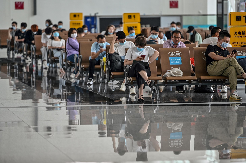 Pasajeros con mascarilla esperan abordar en el aeropuerto de Wuhan, China, el 29 de mayo de 2020