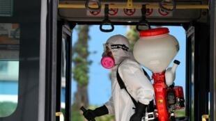 Trabajadores del municipio de Quito realizan la desinfección de varias unidades de transporte de pasajeros que moviliza a los ciudadanos por la capital ecuatoriana, después de que el número de infectados elevó a veinte.