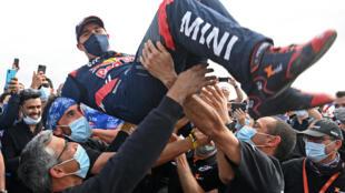Le pilote français Stéphane Peterhansel (Mini), porté en triomphe après sa victoire dans le Rallye Dakar 2021, le 15 janvier 2021 à Jedday=h
