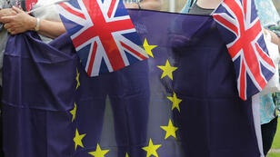 People hold Union Flags and the EU flag at an event organised by pro-Europe 'remain' in central London on June 19, 2016.