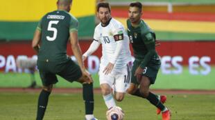 Lionel Messi (C) se escapa de dos bolivianos en el partido entre ambos seleccionados el 13 de octubre de 2020 en La Paz por las clasificatorias sudamericanas para Catar 2022