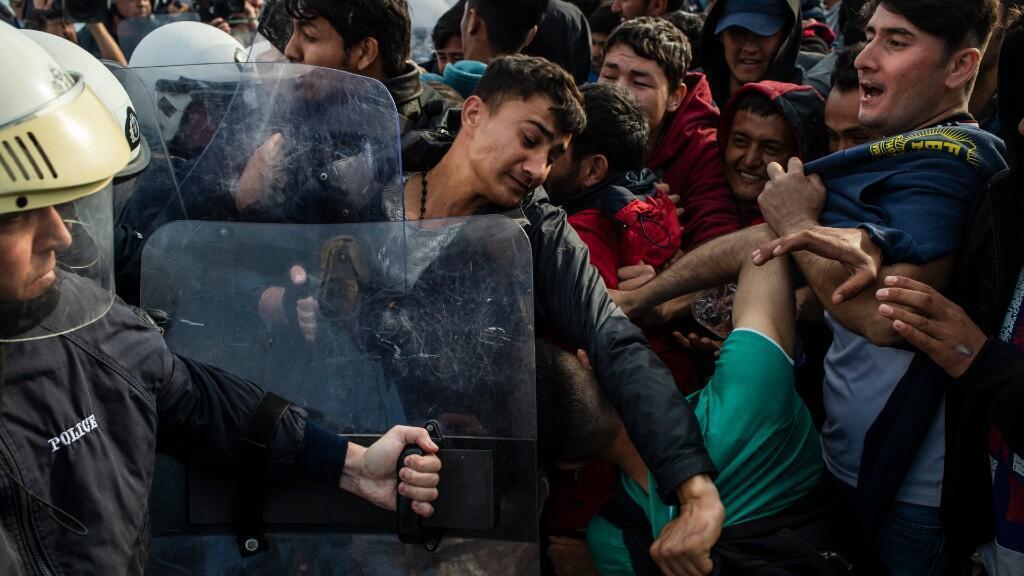 Migrantes y refugiados se enfrentan a la policía antidisturbios en la isla griega de Lesbos, en el Egeo, el 3 de marzo de 2020, en medio de una oleada migratoria procedente de la vecina Turquía, después de que ésta abriera sus fronteras a miles de refugiados que intentaban llegar a Europa.
