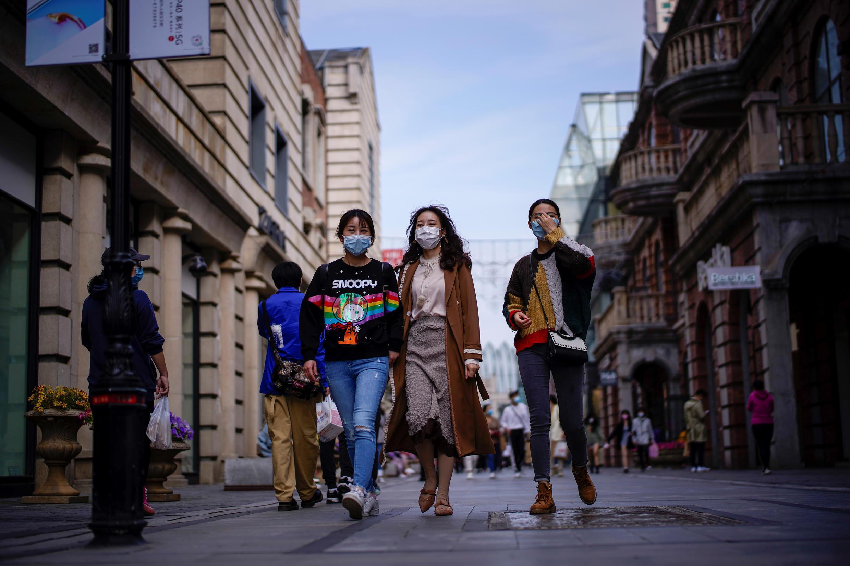 Los residentes de Wuhan pasean por un área comercial el 14 de abril de 2020.