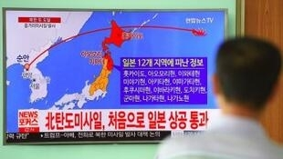 ياباني يشاهد على التلفزيون مسار الصاروخ