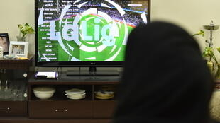 A picture taken January 20, 2020, shows family members watching Qatar's beIN sport channel at their home in the Saudi capital Riyadh